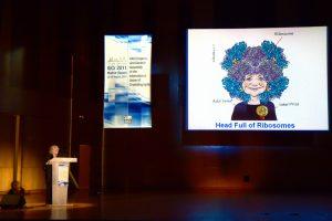 Ada Yonath em 2011, durante congresso científico. Em sua caricatura, os ribossomos substituem seus cabelos cacheados