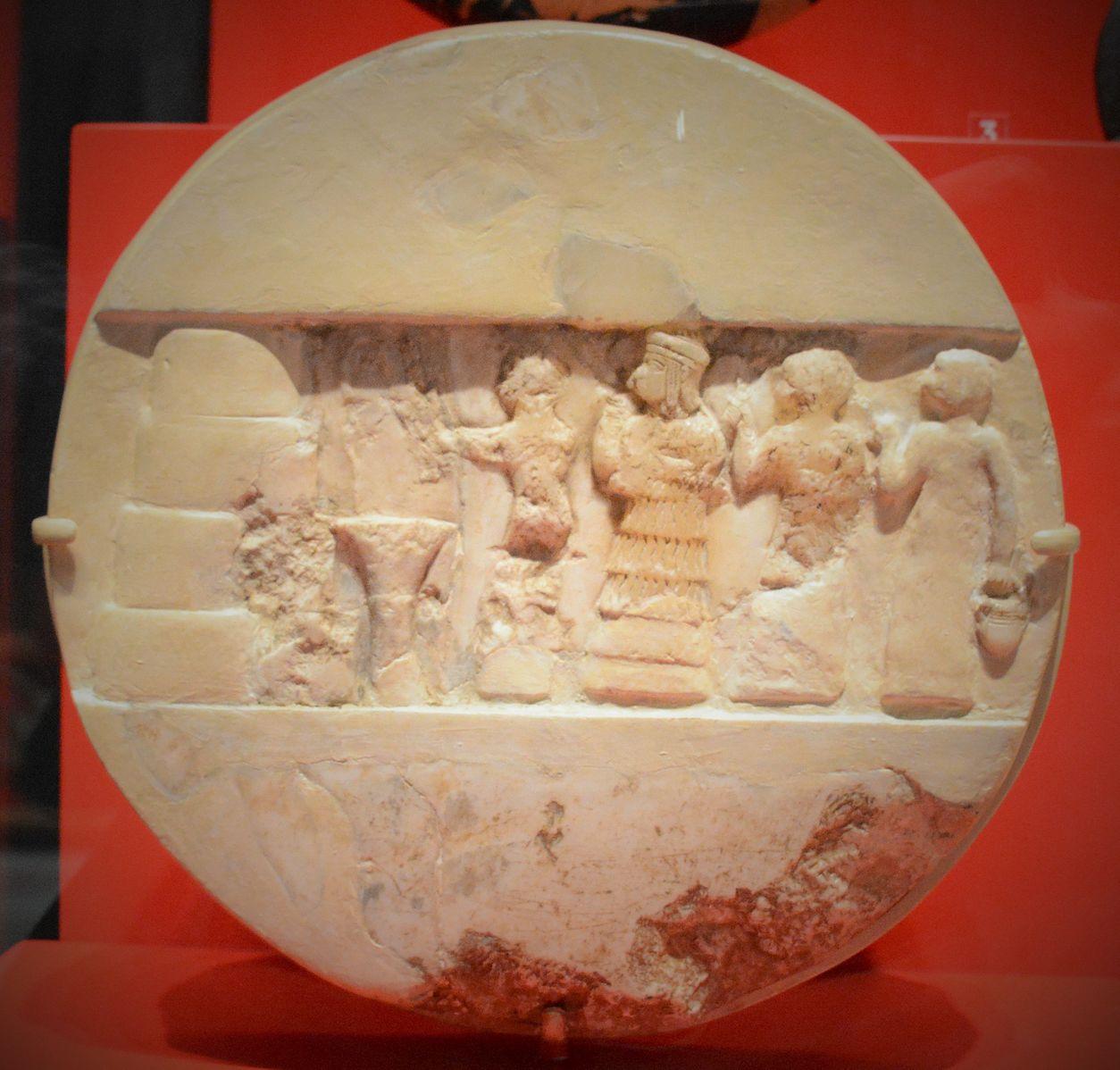 Disco de alabastro de Enheduanna, representada de frente para um suporte de planta durante um ritual. Atrás dela segue um padre e duas sacerdotisas. Unniversity of Philladelphia Museum.