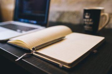 Espaço de trabalho com computador, caderno de notas e caneca.