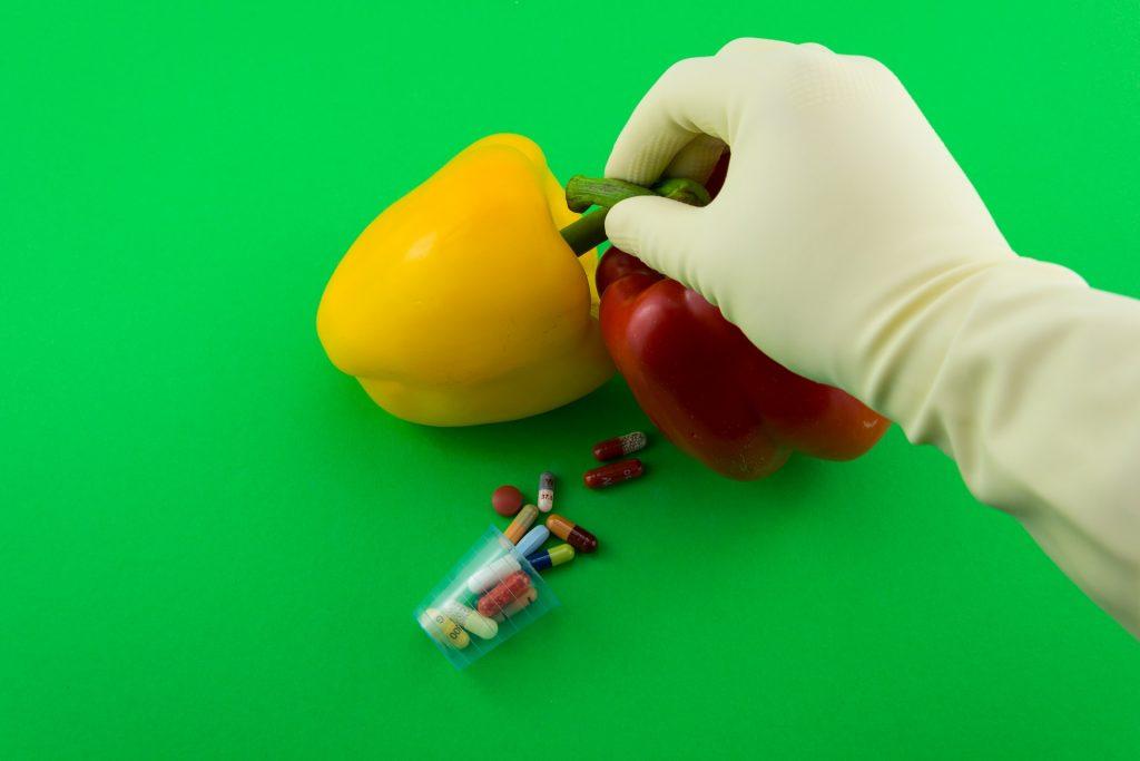 Um pimentão amarelo e outro vermelho, sendo segurados por uma mão com luvas e, ao lado, tem um copo pequeno com alguns remédios dentro
