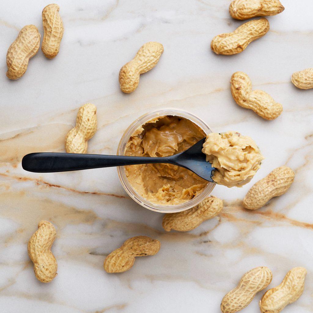 Pode com manteiga de amendoim e uma colher cheia de manteiga de amendoim em cima do pote