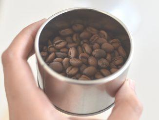 MÃO SEGURANDO COPO COM GRÃOS DE CAFÉ