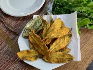um prato com folhas de peixinho frito