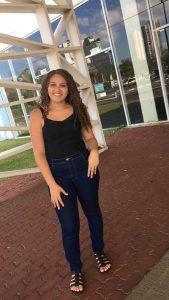 Imagem da aluna Larissa. Ela possui cabelos castanhos cacheados, calças jeans, uma blusa preta de alça e sandálias pretas.