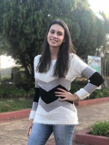 Foto de Kayza em uma rua arborizada. Ela tem cabelos castanhos compridos, usa calça jeans e uma blusa branca com listras cinzas e pretas de mangas compridas.