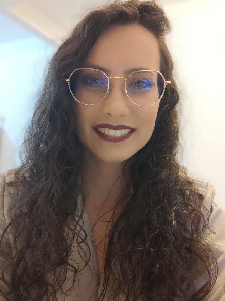 Foto de Kyene Becker. Ela é uma mulher branca de cabelos castanhos compridos e cacheados. Usa óculos de grau redondo e batom roxo na boca, que sorri.