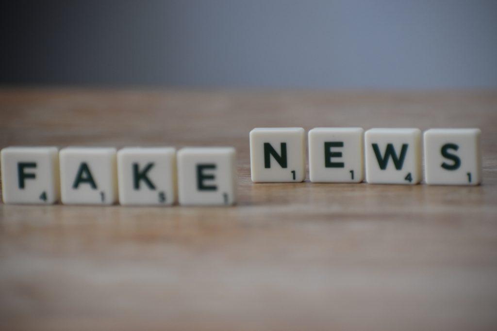 Imagem de blocos brancos com letras do alfabeto escritas em preto formando a palavra Fake News em cima de uma superfície de madeira.