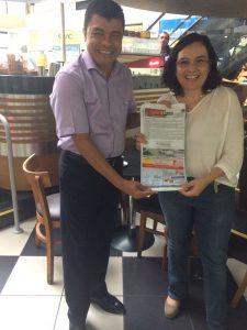 A professora Sheila Elias de Oliveira, coordenadora associada do curso de Bacharelado em Linguística com Roberto Carlos Alves Rodrigues, da empresa Megapão, no lançamento do saquinho de pão em parceria.